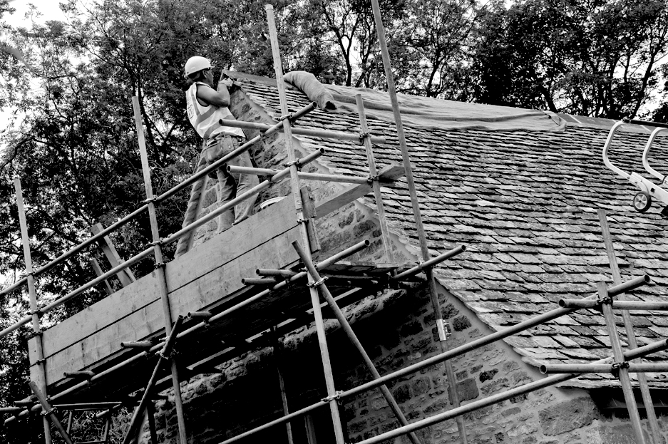 A craftsman up a scaffold tower working on the roof of a large country cottage.