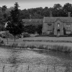 A large country house with a lake in the foreground.